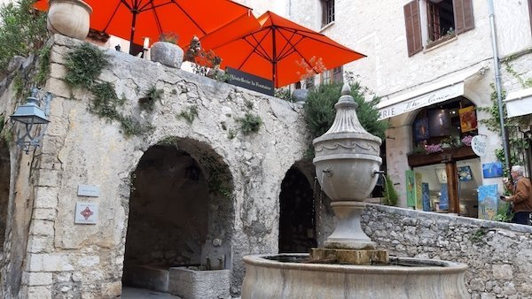 Red awnings and fountain of Hostellerie de la Fontaine St Paul de Vence